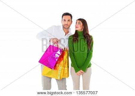 A photo of happy young woman looking at man carrying shopping bags. Male and female partners are in casuals. They are standing isolated over white background.