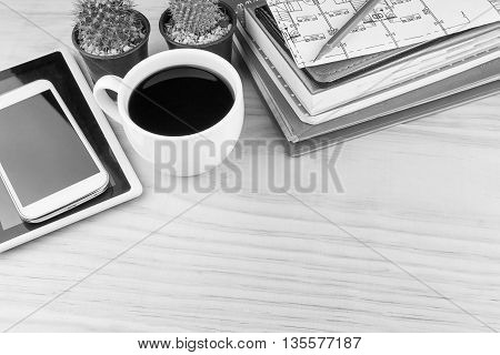 Office desk table with notebooksglasses smart phone and a cactus with cup of coffee.Top view with copy space. Business concept.black and white tone