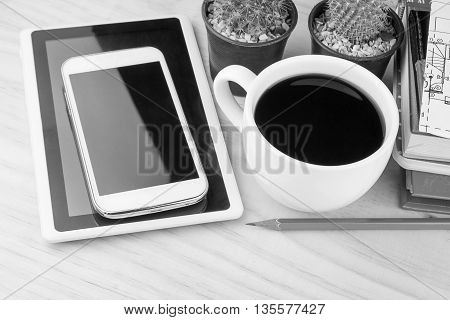 Office desk table with notebooks smart phone and a cactus with cup of coffee.Top view with copy space. Business concept.black and white tone