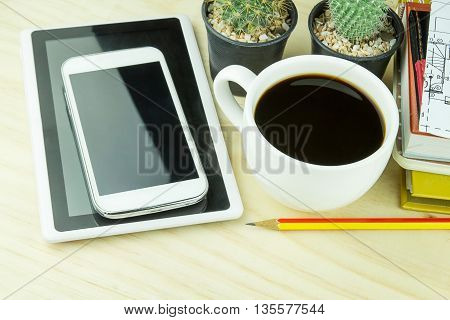 Office desk table with notebooks smart phone and a cactus with cup of coffee.Top view with copy space. Business concept
