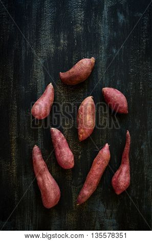 Raw sweet potatoes on a dark rustic background, plenty of copy space