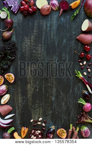 Purple colored fruit and vegetables fresh produce on dark distressed background, plenty of copy space design element for poster, book covers, recipes, website