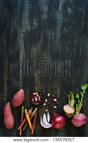 soup vegetables ingredients on dark rustic distressed background, sweet potato, heirloom carrots, kidney beans, onion, turnip