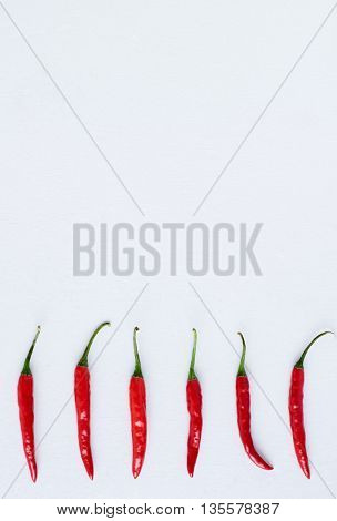 Food background of fresh hot spicy bird's eye chillis on white background, plenty of copy space