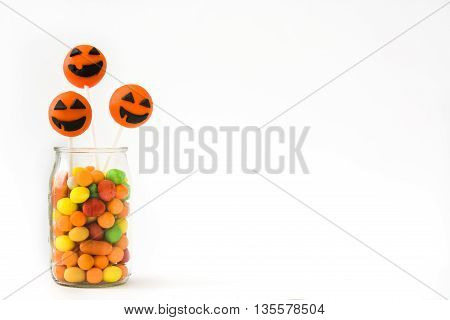Halloween cake pops and colored candies isolated on white background