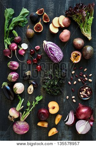 Collection of fresh purple toned vegetables and fruits on dark rustic distressed background, heirloom eggplant, fig, aubergine, cherries, radishes, lettuce, beans passionfruit, cabbage, plum, onion