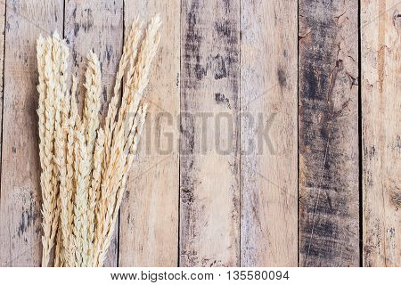 Ears of wheat on a brown wooden table background