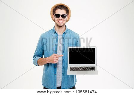 Happy confident young man in sunglasses and hat pointing on blank screen laptop