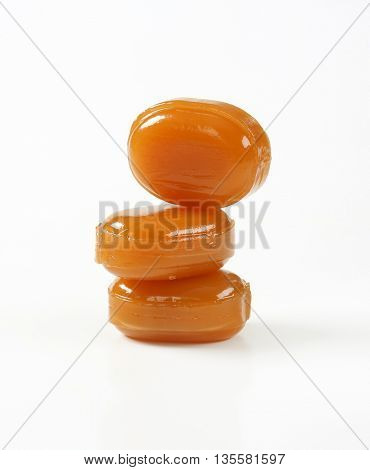 three hard caramel candies on white background