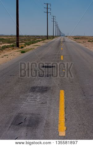 A road with a dashed yellow line leads to the horizon in the desert.