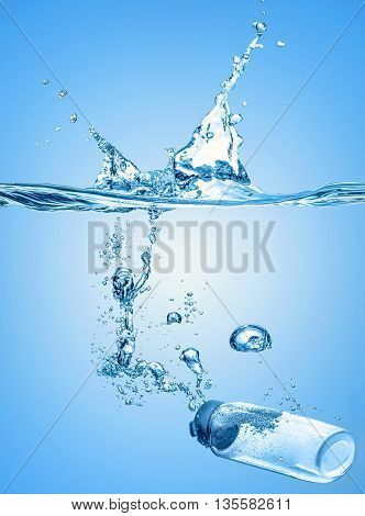 The moisturizing shampoo, cosmetic liquid, tonic, thermal water falls into the blue water with big water splash on the gradient blue water background and with many air bubbles