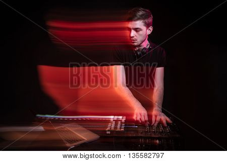 Handsome young dj using laptop and playing music