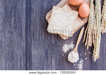 Ears of wheat and egg with slice of bread on a wooden table background