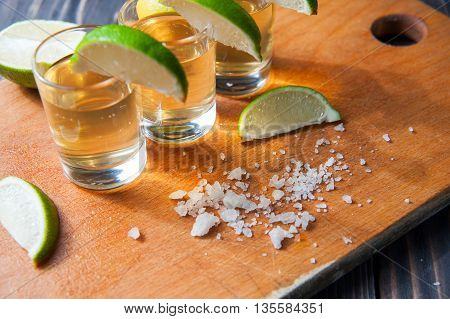 Tequila in Shot Glasses with Lime and Salt on cutting board