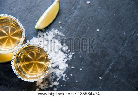 Tequila shots with lime sliceand salt, top view
