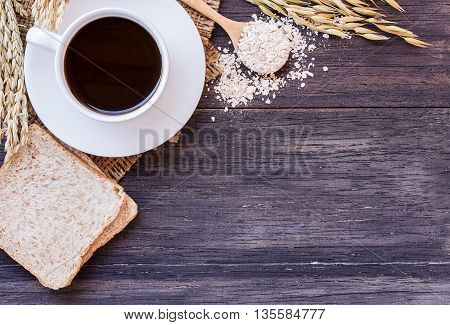 Ears of wheatcoffee and egg with slice of bread on a dark wooden table background