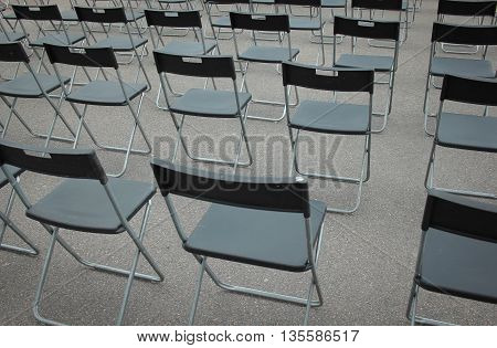 Many black folding chairs in the street