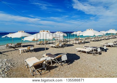 colorful beach umbrellas with deck chairs pebble beach and island in distance