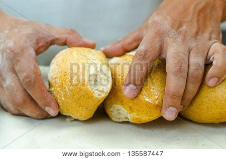 Bakers hands stacking fresh delicious buns of bread against each other.