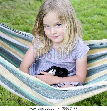 Child blond girl sitting in a hammock and holding her guinea pig