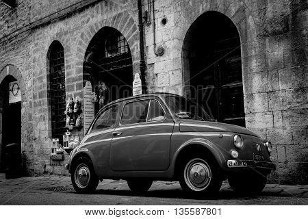 Gubbio, Italy - May 13, 2011; Gritty monochrome image traditional back Italian street with iconic small car surrounded by old stone buildings vignette