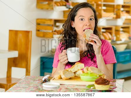 Pretty brunette woman sitting at table inside bakery, holding cup of coffee and biting into bread slice.