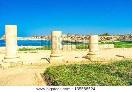 The large archaeological site located on the mediterranean coast is seen through the ruined columns of the ancient Temple Caesarea Israel.