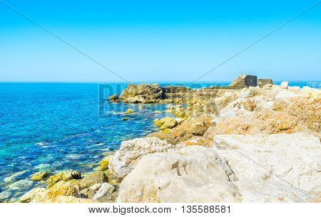 The rocky shore of Caesarea with the ancient building ruins on the background Israel.