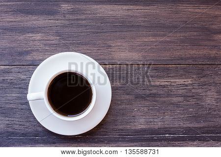 Cup of coffee on dark wooden table background top view with copy space