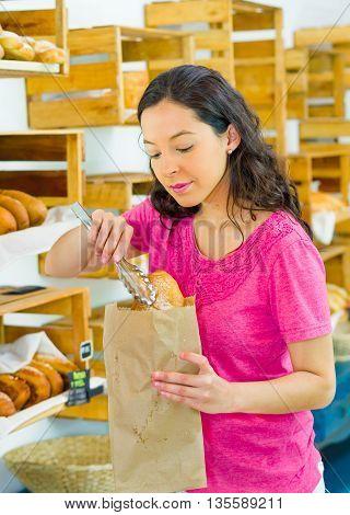 Pretty brunette wearing pink shirt placing bread inside brown paper bag, customer bakery concept.
