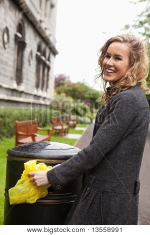Woman putting plastic waste in garbage bin