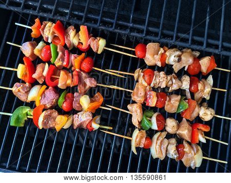 Meat and vegetable skewers on a grill. Outdoor barbecue.