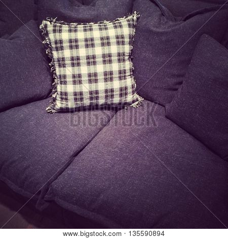 Stylish checked cushion on a dark gray textile sofa.