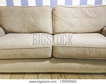 Soft beige sofa near the wall with striped wallpaper. Comfortable furniture.