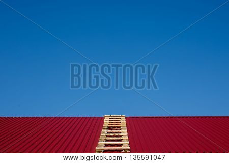 ladder on the gable roof. wooden ladder lying on the rooftop. clear blue sky. fix the roof before it starts to rain. go through the roof. copy space for your text