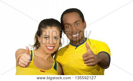 Charming interracial couple wearing yellow football shirts giving thumbs up to camera, white studio background.