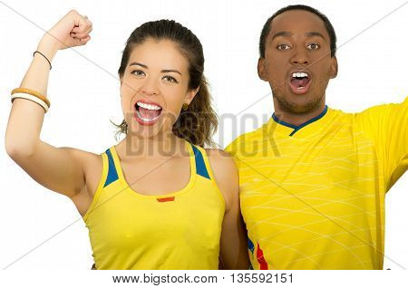 Charming interracial couple wearing yellow football shirts cheering joyfully to camera, white studio background.