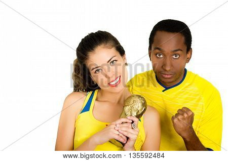 Charming interracial couple wearing yellow football shirts holding small trophy posing for camera, white studio background.