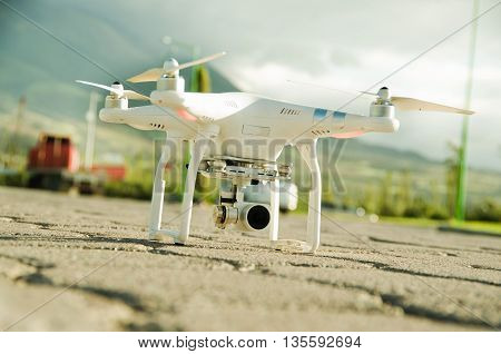 White drone with camera mounted underneath sitting on concrete surface, mountain landscape background.