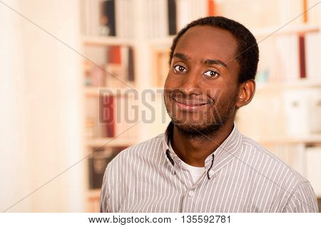Handsome man wearing casual clothes posing smiling for camera, white bookshelves background.
