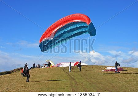 Paragliders preparing to launch their wings to fly