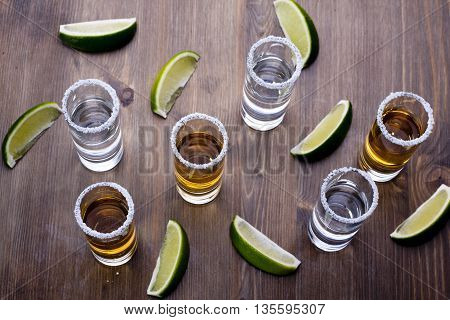 Six shots of tequila on a wooden table
