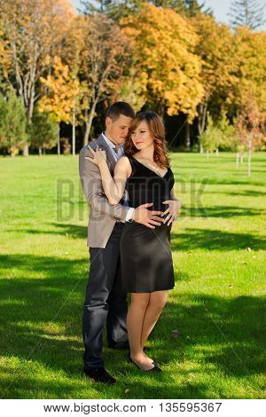 Man tenderly embraced Pregnant Woman outdoors in the countryside