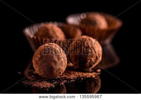 Chocolate truffles on black background, studio shot