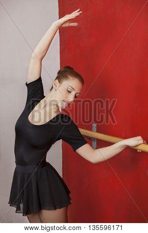 Ballet Dancer Stretching At Barre In Studio