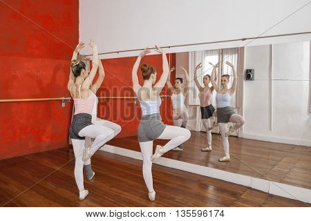 Dancers Performing While Looking At Mirror At Ballet Studio