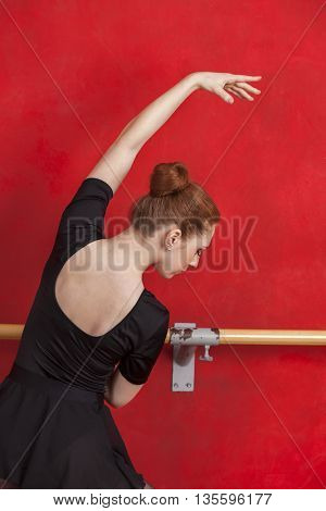 Ballerina Performing Against Red Wall