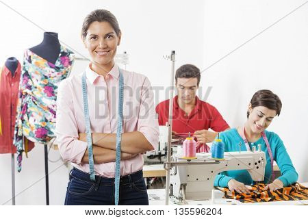 Confident Tailor With Arms Crossed Standing In Factory