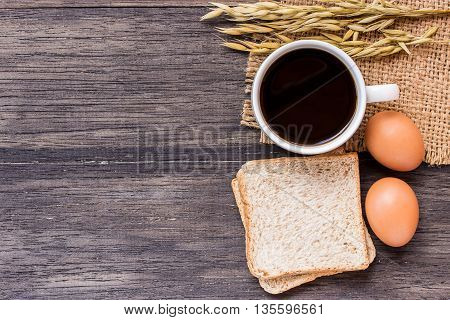 Ears of wheategg and coffee with slice of bread on a dark wooden table background.top view with copy space