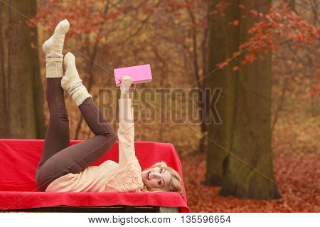 Woman Relaxing In Autumn Fall Park Reading Book.